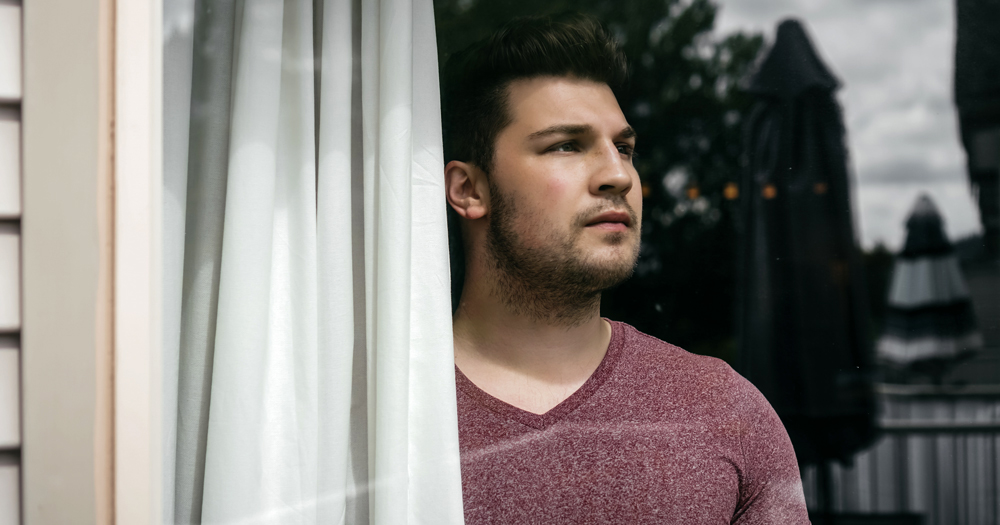 New survey launched in Ireland to look at the impact of lockdown for LGBT+ people: Man looking outside of his window.