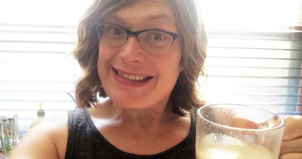 Lilly Wachowski smiling while holding a coffee