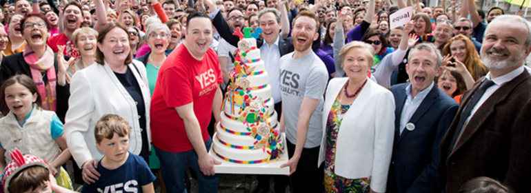 Crowds celebrate the Yes anniversary vote in the same-sex marriage referendum at Dublin Castle with a giant Yes cake