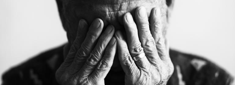 An old man clutches his hands to his face because pension equality is far from here