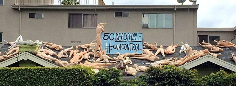 WeHo artist's installation on a rooftop showing 50 mannequins strewn about a rooftop, with the sign 50 Dead People # Gun Control