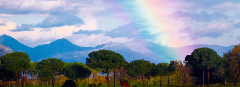 a mountainside with a rainbow