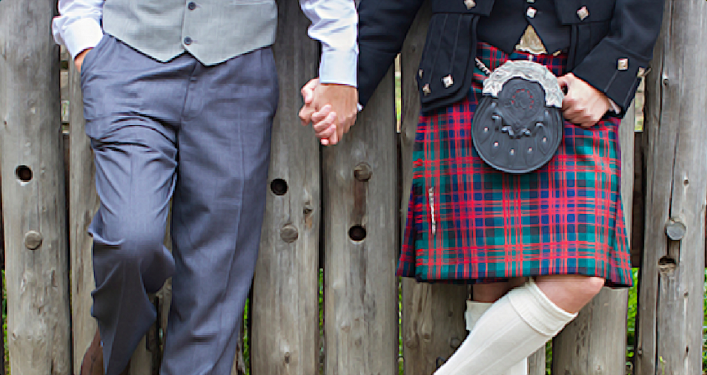 Two men, one dressed in a suit the other in a kilt, holding hands in front of a fence