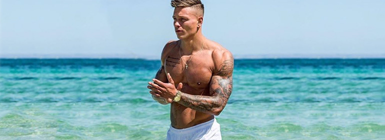 Alex Bowen, who has a naked selfie online, topless on a beach with bright blue water in the background