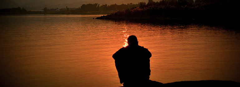 A lonely person sitting by the edge of the lake after reading the RCNI report on sexual violence