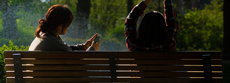 Two girls in a park on a bench thanks to GCN's Top 5 Romantic Date Ideas: Dublin guide