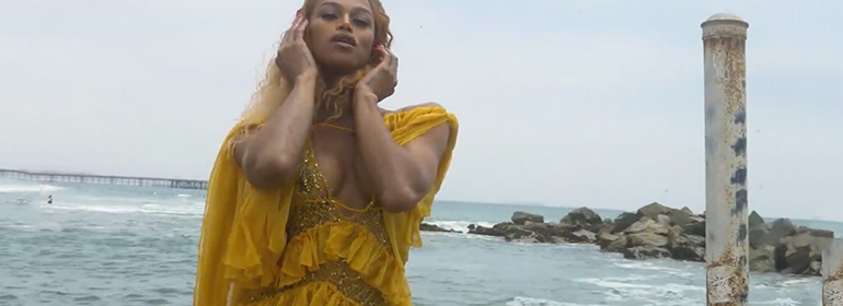 Trans Beyoncé Impersonator in a yellow dress at the sea