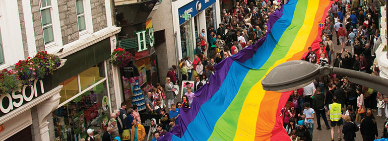 Galway pride 2016 parade with a giant rainbow flag over crowds of people.