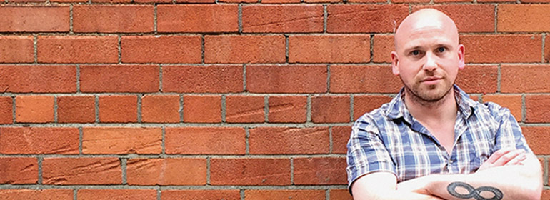 The poet and journalist Rob Buchanan standing in front of a red brick wall with his arms folded