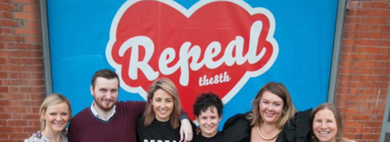 The replica of Maser's repeal the 8th mural at ICCL with people standing in front of it smiling