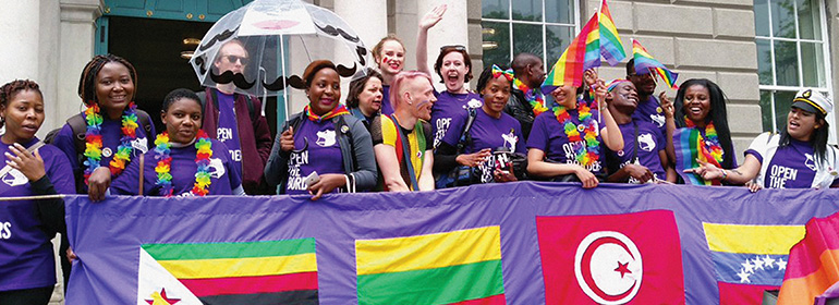 LGBT Asylum seekers at Dublin Pride holding a banner with nations' flags and wearing purple t-shirts