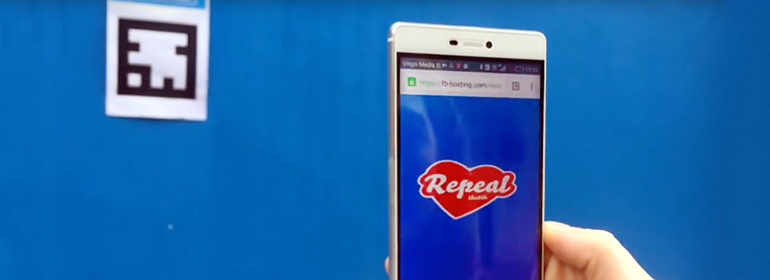 The 8Mural QR code on a blue wall with a repeal the 8th mural on a phone screen
