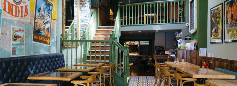 James kavanagh reviews Pickle, the restaurant pictured here. They have wooden chairs, with leather coated benches, and green painted wooden banisters
