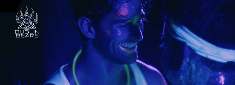 A neon party with a guy smiling under UV light for the bear city 3 irish premiere with Dublin Bears