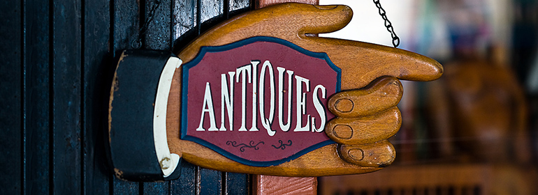 An antiques sign in a wooden hand pointing the way to the national antiques art and vintage fair