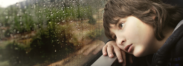a boy looking sadly out a window just like the 5 children of lesbian couple are sad because their mom received homophobic abuse