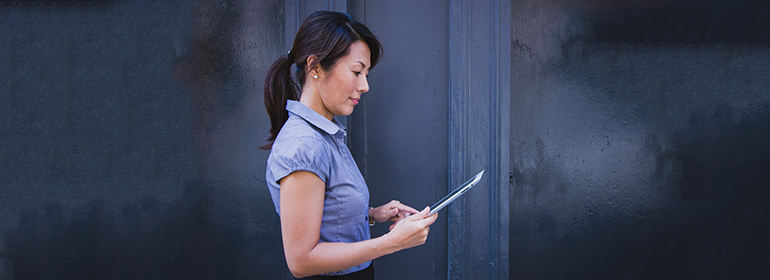 A woman at work in a blouse using a tablet, just like the LGBT in the workplace nowadays