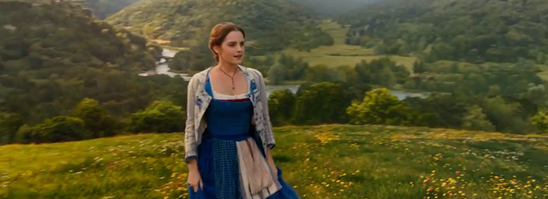 Emma watson as Belle in the new Beauty and the Beast trailer standing on a lush green mountainside in a blue and white dress, one of the stories in today's Cuppán Gay