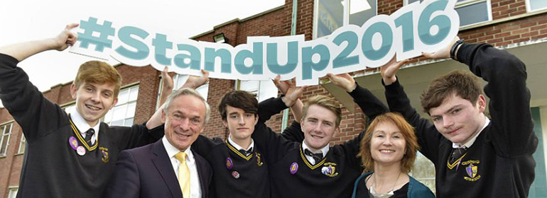 Minister for Education Richard Bruton, students and Moninne Griffith launching Stand Up 2016 holding a giant #StandUp2016 sign