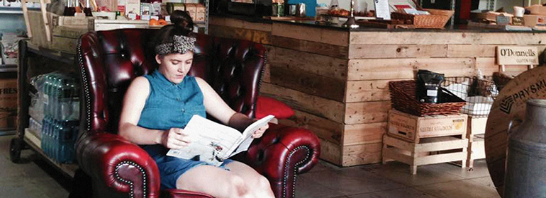 A girl reading a book in a red leather chair in Bang Bang cafe