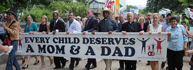 National Organisation for marriage supporters holding a sign saying every child deserves a mom and a dad, like the NOM story in today's Cuppán Gay