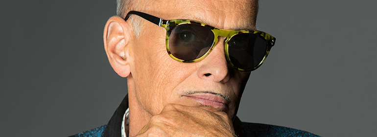 John Waters wearing sunglasses and with his hand on his chin, who will be at outburst arts queer festival this year (2016)