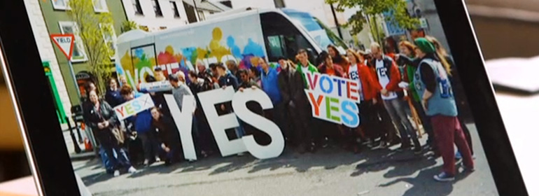The Only Gay In The Village shot showing a vote yes equality team holding the giant YES letters