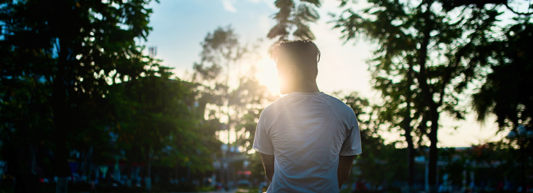 A man sitting in front of trees with the sun shining behind him, signifying that HIV and sexual confidence can go hand in hand
