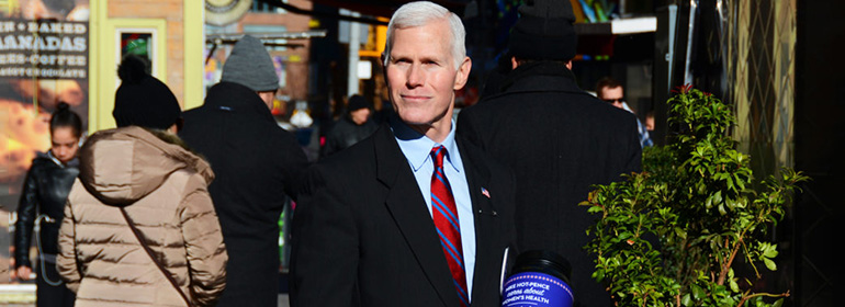 Mike Hot-Pence in a suit holding a donation bucket who is one of today's Cuppán Gay posts