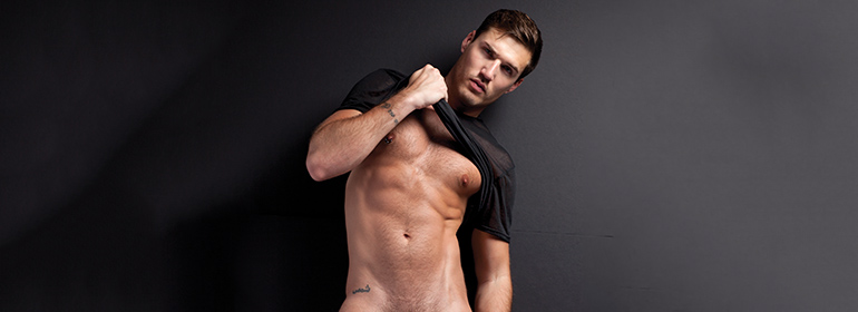 Irish porn star Theo ford in a black t-shirt pulling it up so his abs are revealed