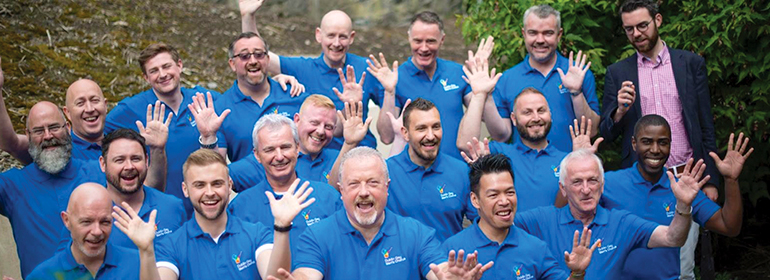 The Dublin Gay Men's Chorus in blue t-shirts singing for the queer christmas concerts that are planned in December