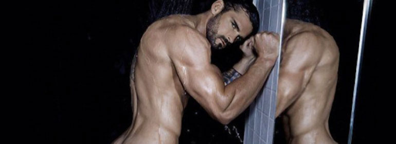 Stuart Reardon naked standing against a shower wall in today's Cuppán Gay