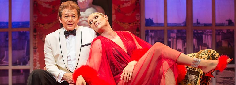 The two star performers in La Cage aux follies, one in a white tux and John partridge in drag in a flowing, see-through red gown