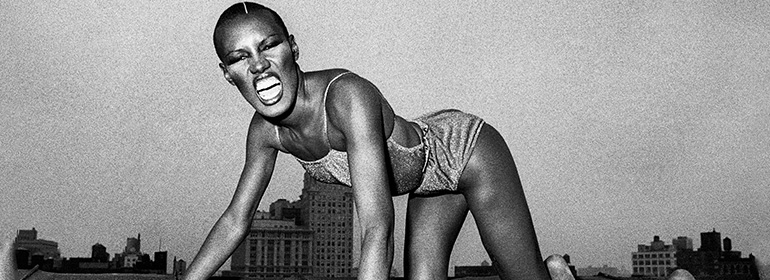 Grace Jones on her hands and knees as a giant, the same artist who is featured in today's Cuppán Gay