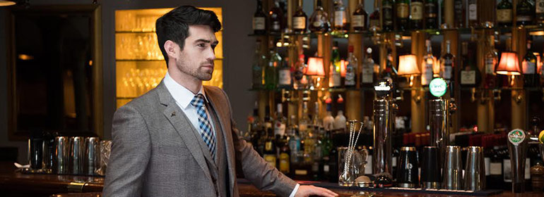 A groom in a suit at the Marco Pierre White Courtyard Bar and Grill Wedding showcase standing at the bar