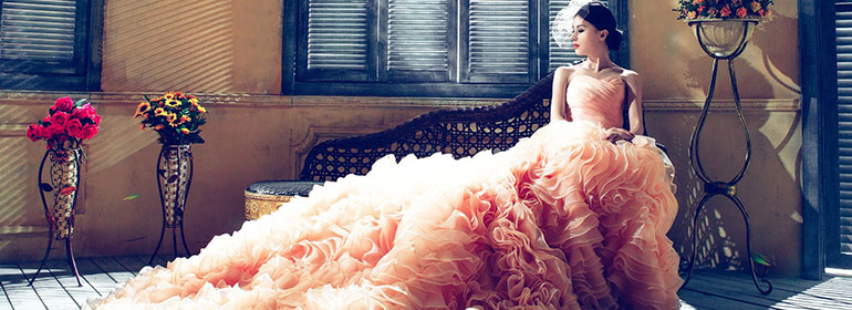 A woman in a peach coloured, ruffly ball gown who could be going to the Glória choir gala