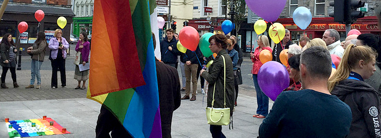 People at the mullingar pride event with rainbow flags and rainbow balloons
