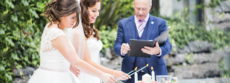 Two brides in wedding dresses lighting a candle together with a man in a blue suit acting as their celebrant
