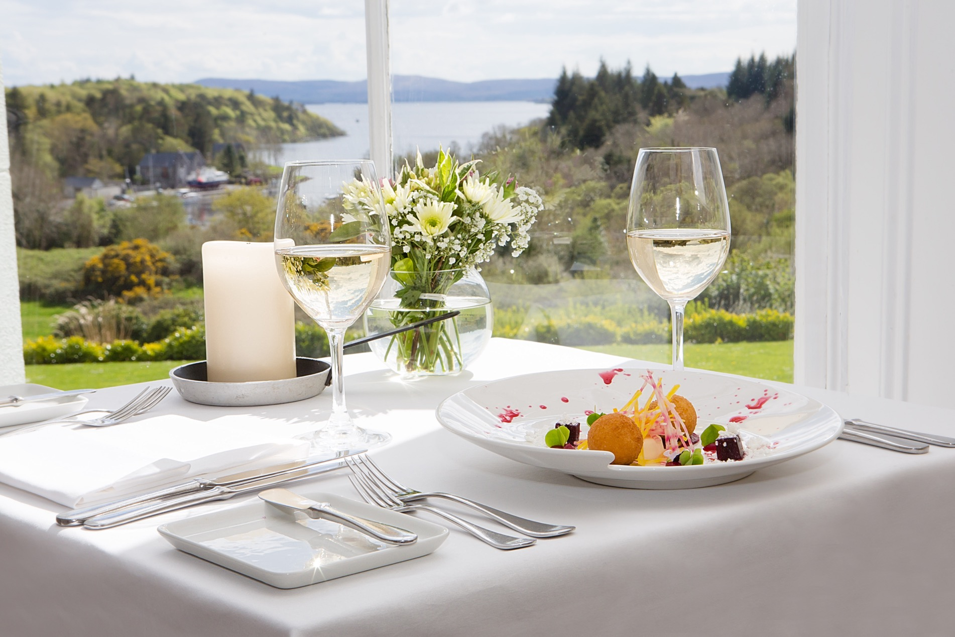 An interior shot of the lodge at ashford castle where if you book a wedding, you could win a luxury cruise to the value of e10000 with wine glasses and food on a white table with cutlery