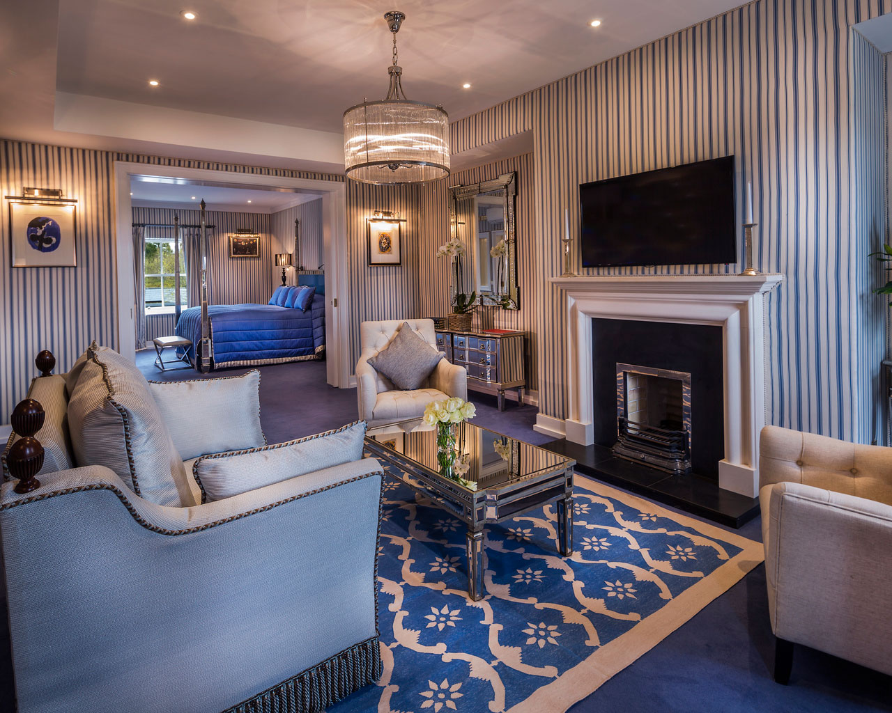 An interior shot of the lodge at ashford castle where if you book a wedding, you could win a luxury cruise to the value of e10000 with a blue bed, chairs and a fireplace