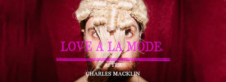 A bearded man in a blonde 18th century wig against red curtains as a poster for Love à la Mode