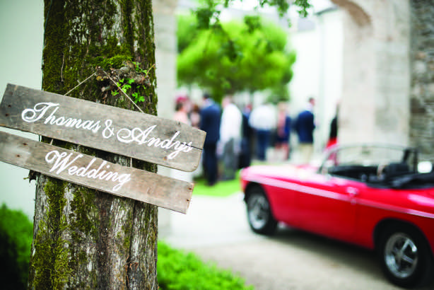 Thomas & Andrew's Wedding sign on a tree with a red car and people visible in the background from Andrew and Thomas' Real Weddings article