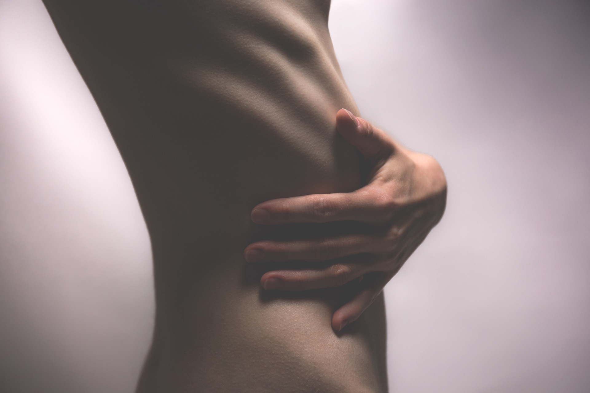 A non-clothed person clutching their ribs to show that they're sex positive