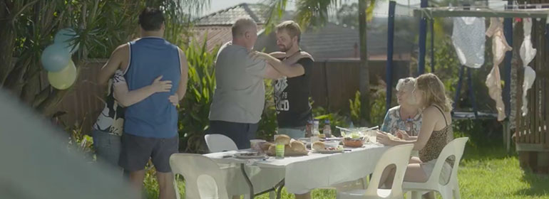 A dad embraces his son at a family dinner party in a cute Mardi Gras ad which is one of today's Cuppán Gay stories