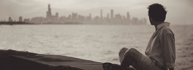 an LGBT person looking at a chicago skyline because they still need to leave ireland to express their sexual and gender identities (in black and white)