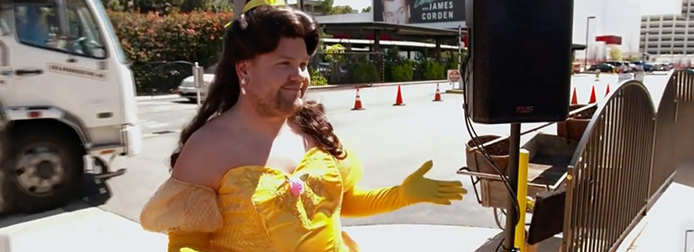 James Corden dressed as Belle from Beauty and the beast in a yellow dress and brown wig which is one of the stories in today's Cuppán Gay.