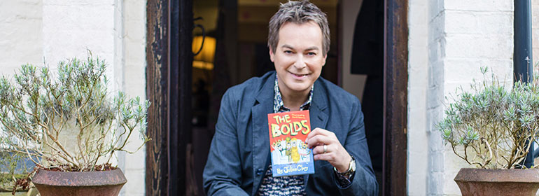 Julian Clary holding up a book
