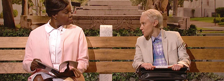 Kate McKinnon as Jeff Sessions sitting on a bench with a woman which is one of the stories in today's Cuppán Gay