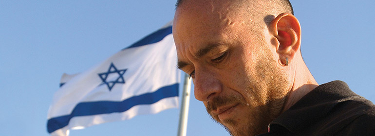 A still from the film Who's Gonna Love Me Now with the subject of the film standing in front of an Israeli flag