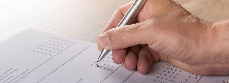 A person filling out a diaspora postal vote ballot